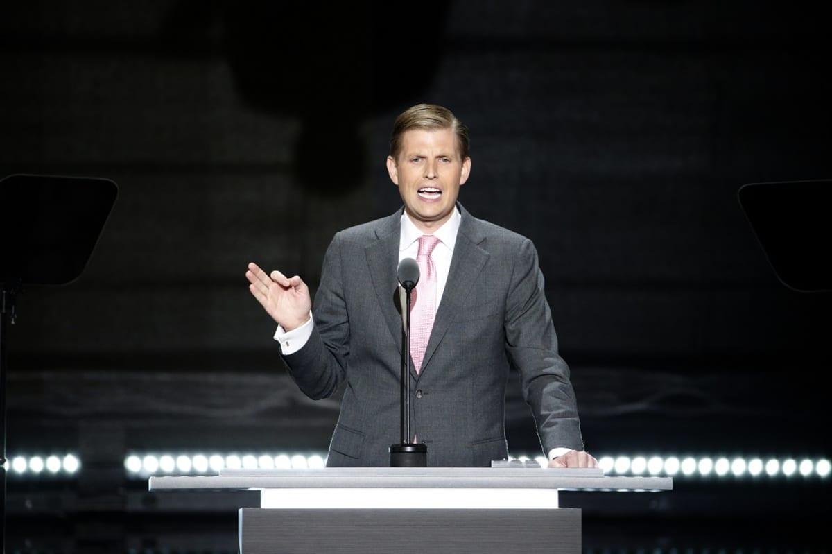 Puolikuva Ericistä, pitää puhetta puhujapöntössä, tumma tausta.
