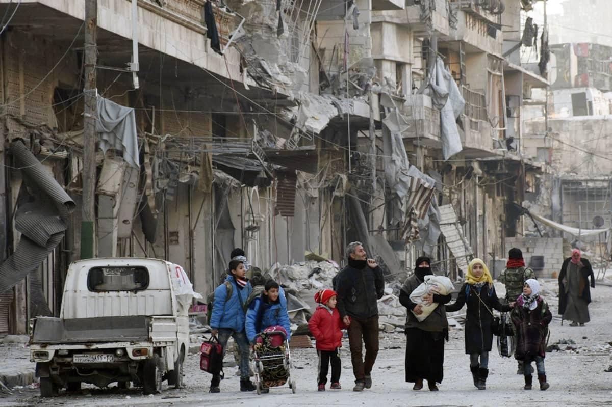 Ihmisiä kävelee talonraunioiden keskellä Aleppossa.