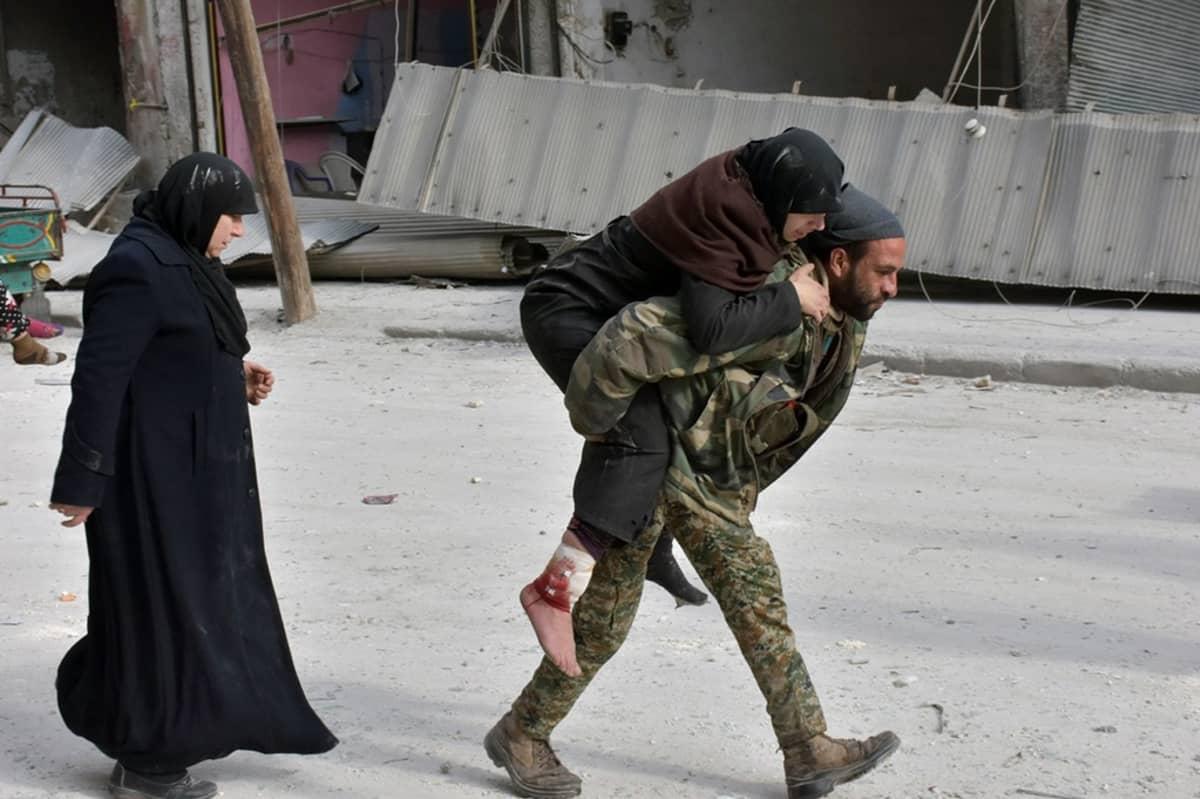 Syyrialainen sotilas kantaa loukkaantunutta naista.
