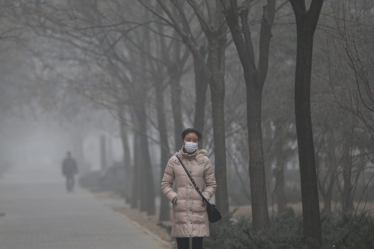 Kiinalaisnainen kävelee pekingiläisessä puistossa maski kasvoillaan.