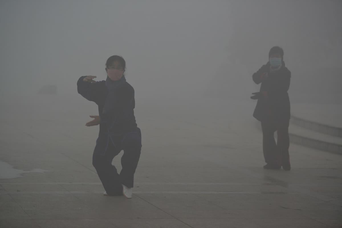 Kaksi naista voimistelevat vahvan saastesumun peittämässä Pohjois-Kiinassa.