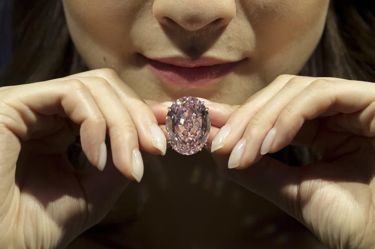 Kuvassa maailman korkeimmalla hinnalla myyty jalokivi. Nainen pitää timanttia sormiensa välissä.