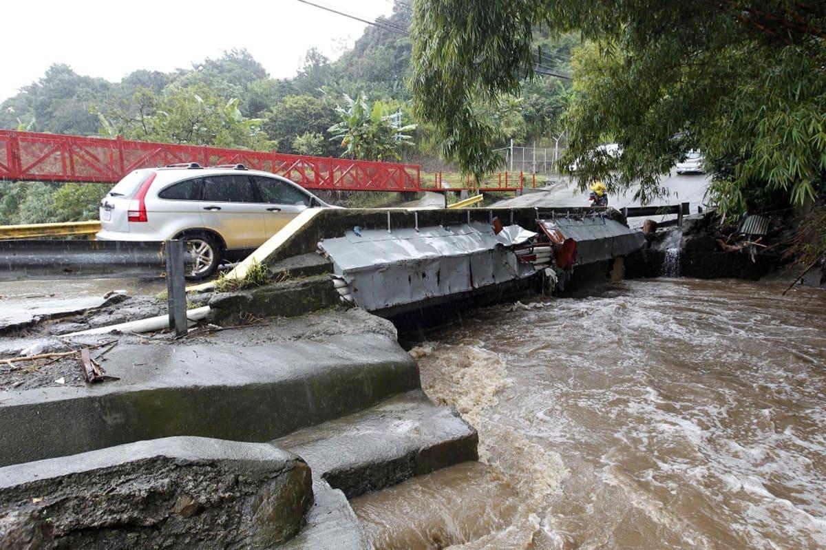Auto ylittämässä siltaa tulvivan joen siltaa.