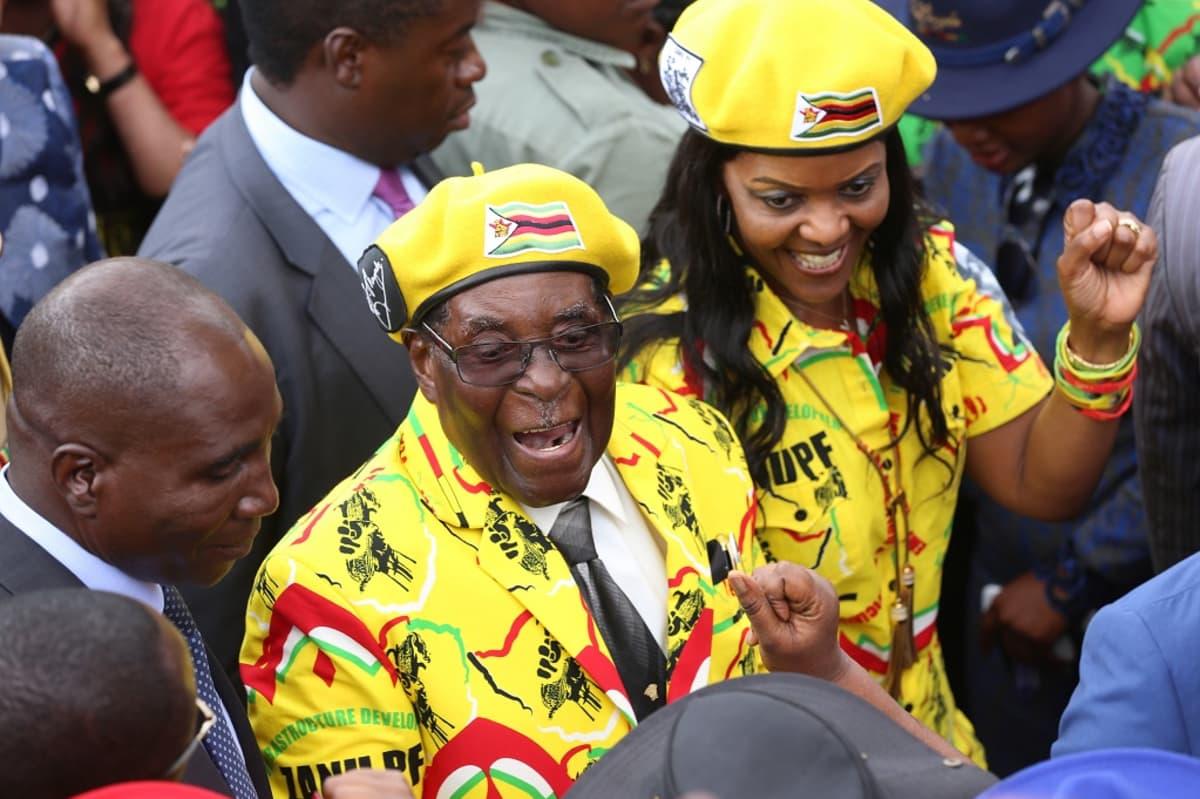Mugabet puolueensa kokouksessa iloisenkeltaisissa asuissa väkijoukon keskellä.