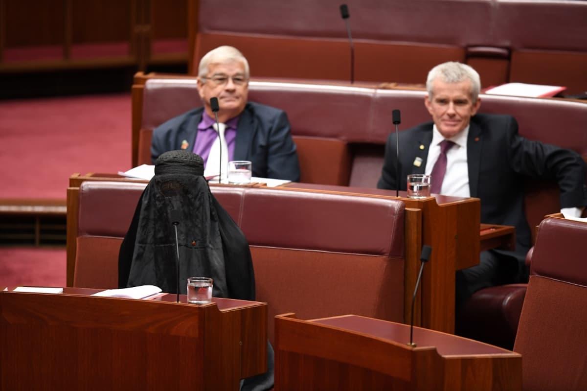 Kuvassa Pauline Hanson istuu parlamentissa burga päällään. Hänen takanaan istuu kaksi miestä.