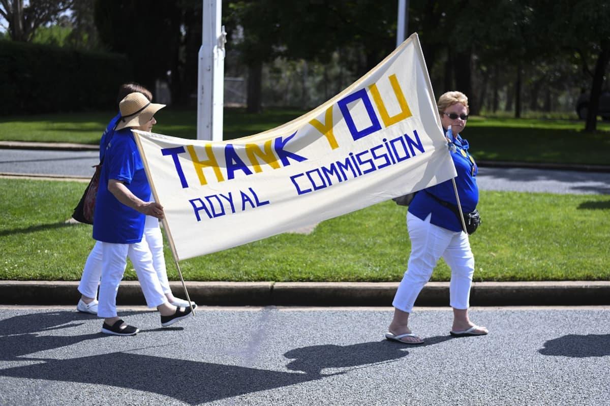Australian ja Uuden-Seelannin orpokotilasten etujärjestö CLAN:in jäsenet kiittivät kyltissään tutkimuskomissiota.