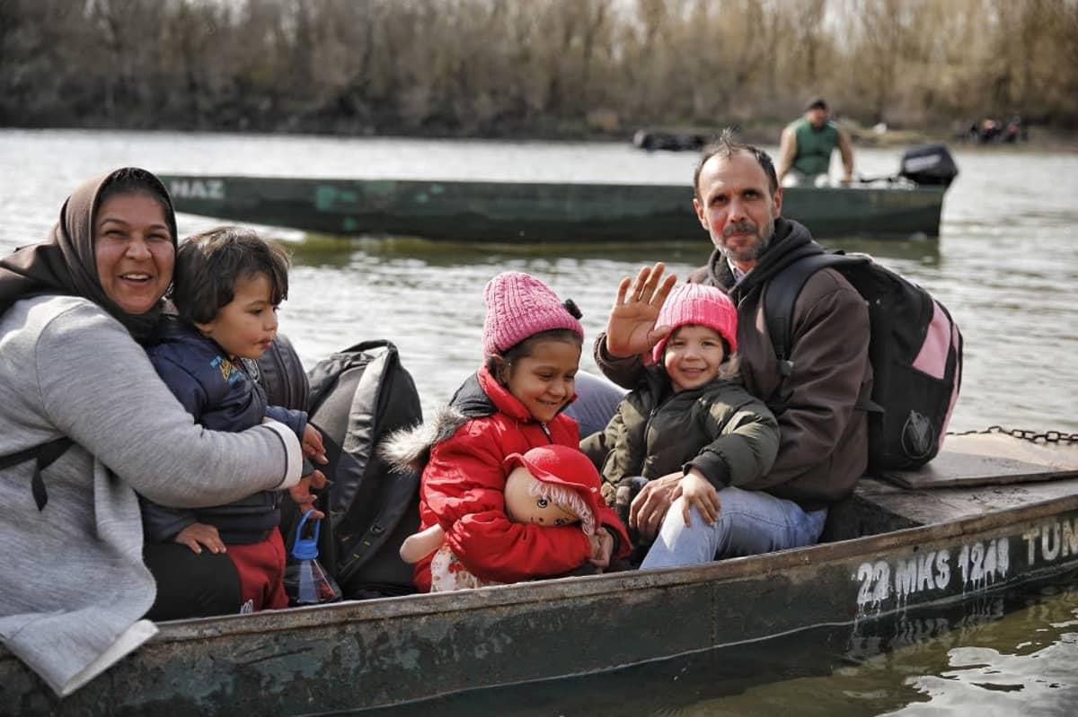 Ihmiset ylittivät Turkin ja Kreikan välisen rajajoen pienellä veneellä.