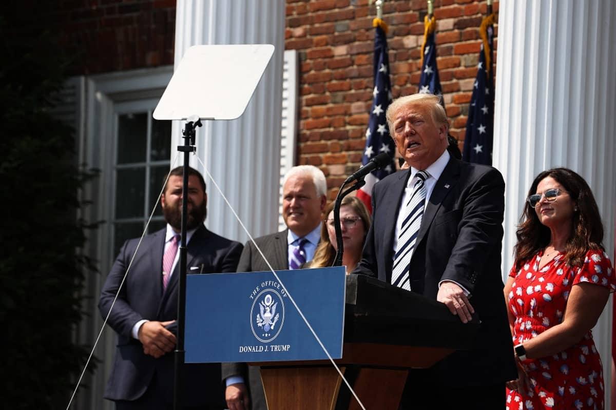 Kuvassa Donald Trump seisoo puhujanpöntön takana. Hänen takanaan on neljä ihmistä.