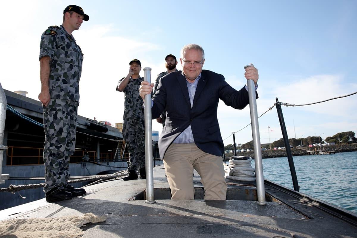 Kuvassa keskellä Australian pääministeri Scott Morrison menossa sukellusveneeseen. Hänen vasemmalla puolellaan seisoo yksi sotilas ja hänen takanaan kaksi sotilasta.