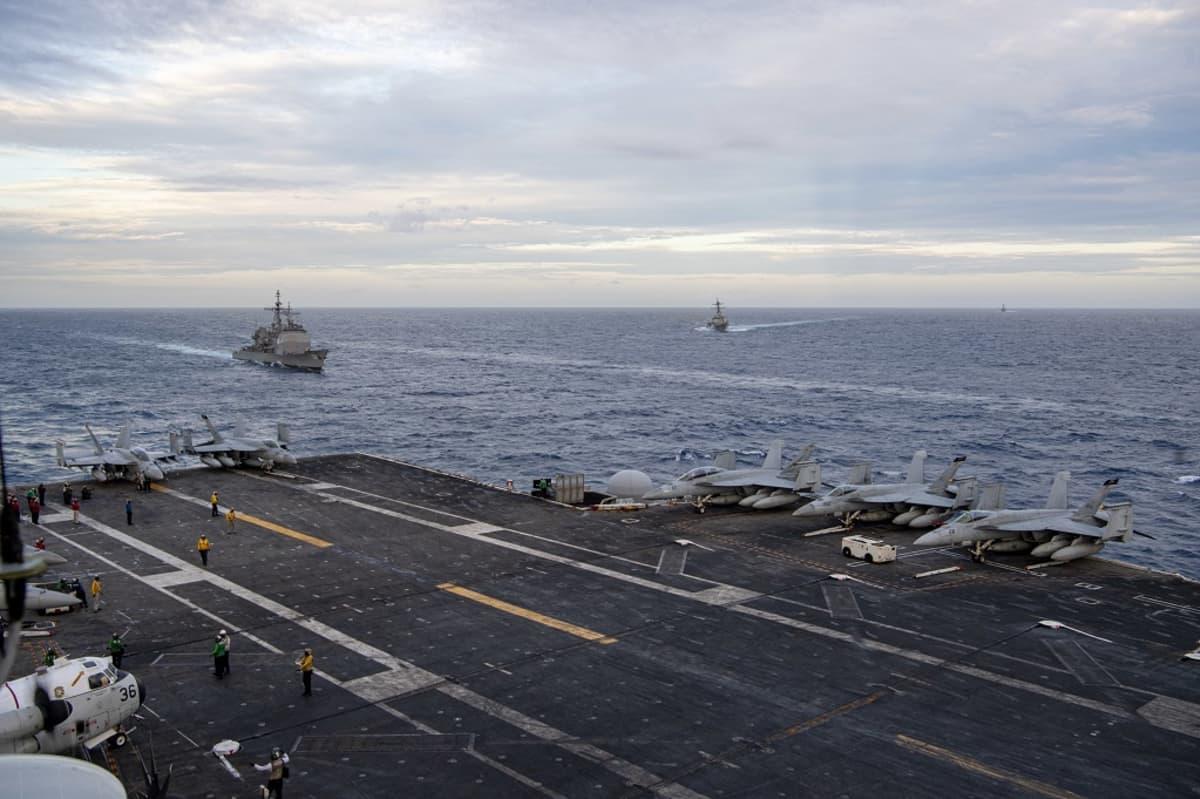 Kuvassa on Yhdysvaltojen lentotukialus, jonka takana näkyy kaksi sotalaivaa.