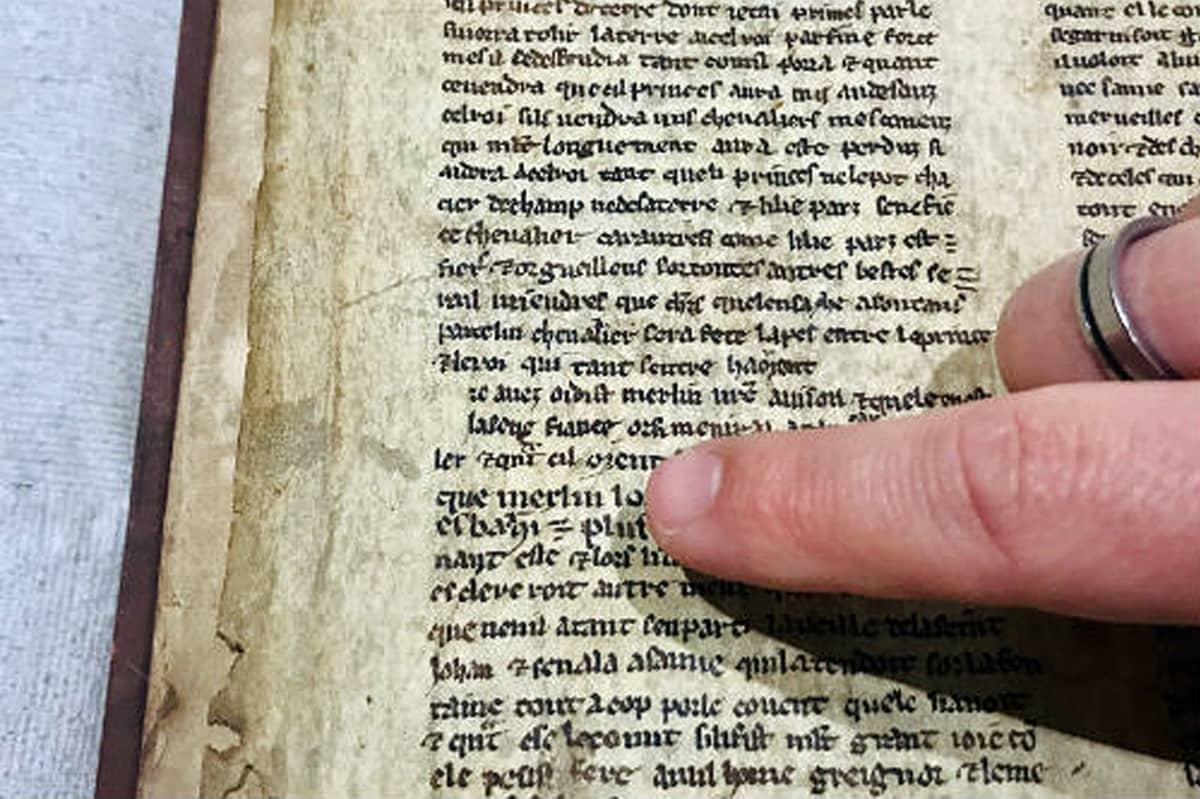 """Sormi osoittaa vanhalla ranskalla kirjoitetun tekstin riviä, joka alkaa """"que Merlin..."""""""
