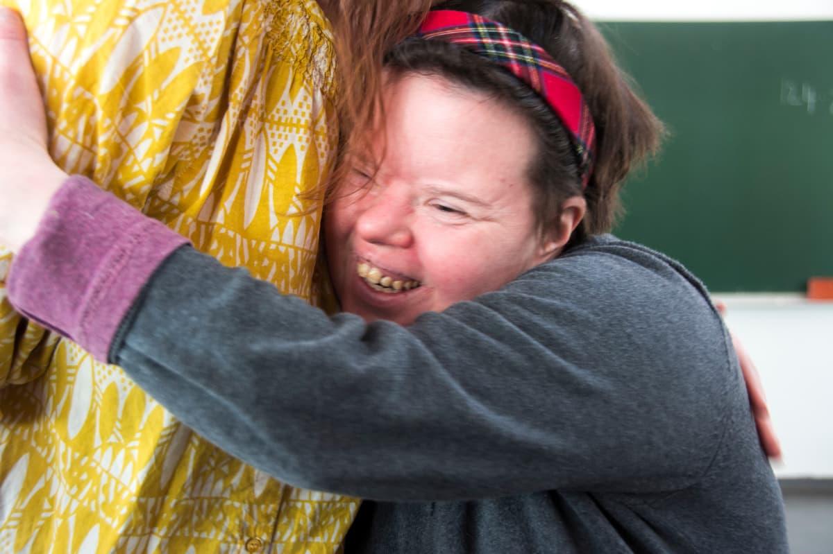 Niina Kivelä halaa yhteisömuusikko-opettajaansa.