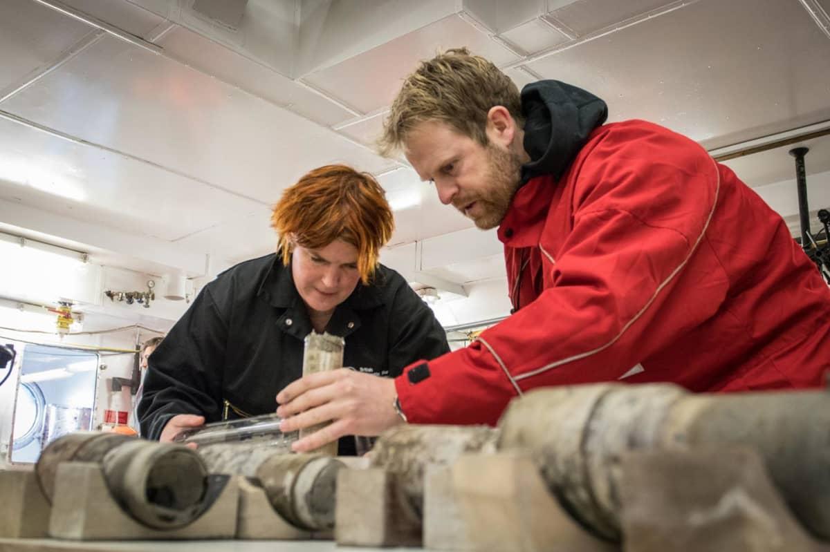 Kaksi tutkijaa kumartuneena merenpohjasta kairattujen putkimaisen maanäytteiden ylle.