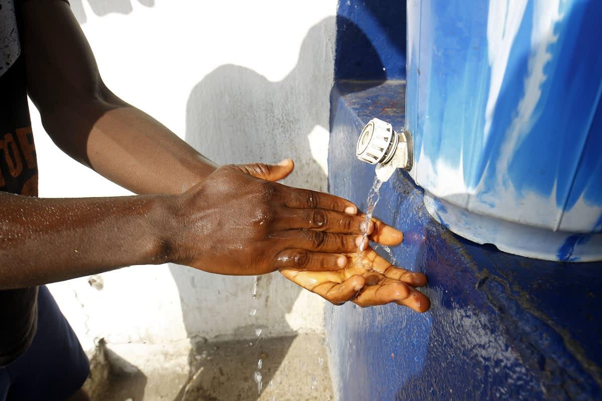 Käsien pesus sinisestä muovitankista tulee vettä.