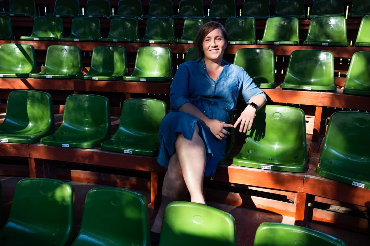 Nainen katsoo kohti kameraa. Nainen istuu tyhjässä vihreäpenkkisessä katsomossa, aurinko paistaa.