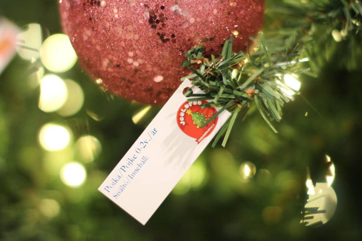 Joulukuusesta roikkuu joulukoriste ja pakettikortti.