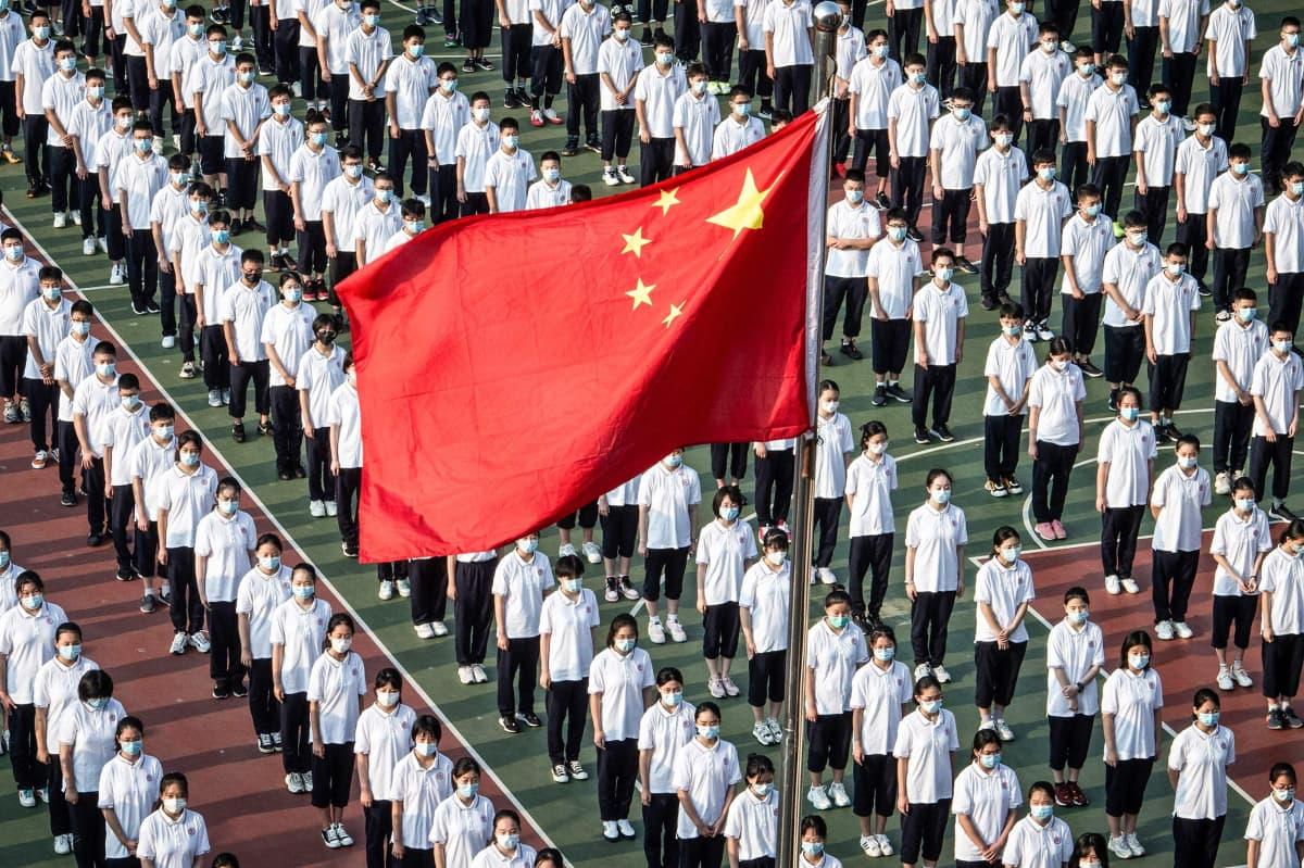 Kiinan lippu salossa ja nuoria ihmisiä taustalla.