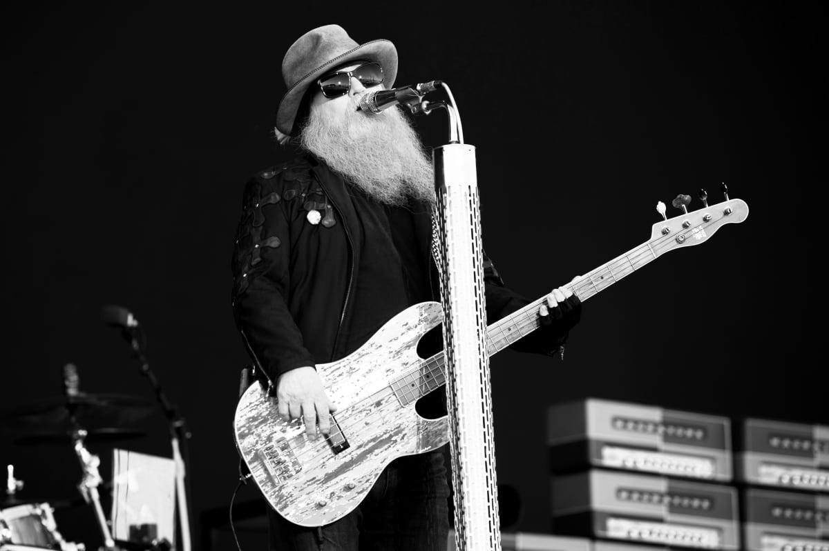 Rockbandet ZZ Tops basist Dusty Hill står på en scen och sjunger i en mikrofon. Bilden är tagen på en festival 2019.