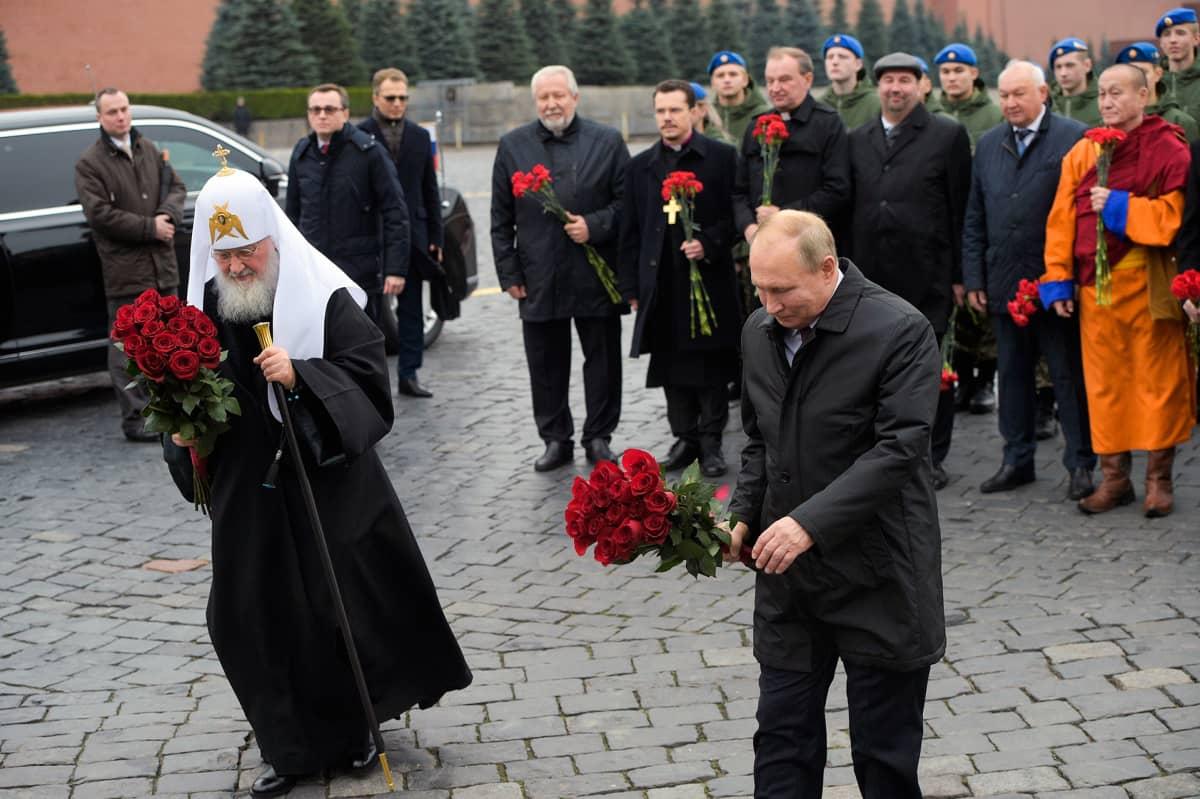 Kuvassa Venäjän ortodoksisen kirkon johtaja patriarkka Kirillja presidentti Vladimir Putin. Molemmilla on käsissään kukkakimput.