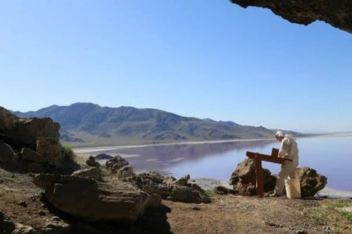 Arkeologi seulomassa maata luolan suulla. Taustalla järvi ja kumpuileva ranta.