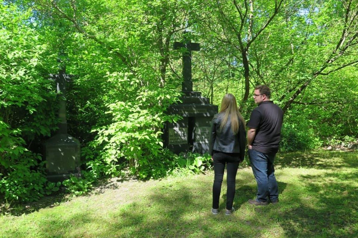 hautakiviä katselee kaksi ihmistä
