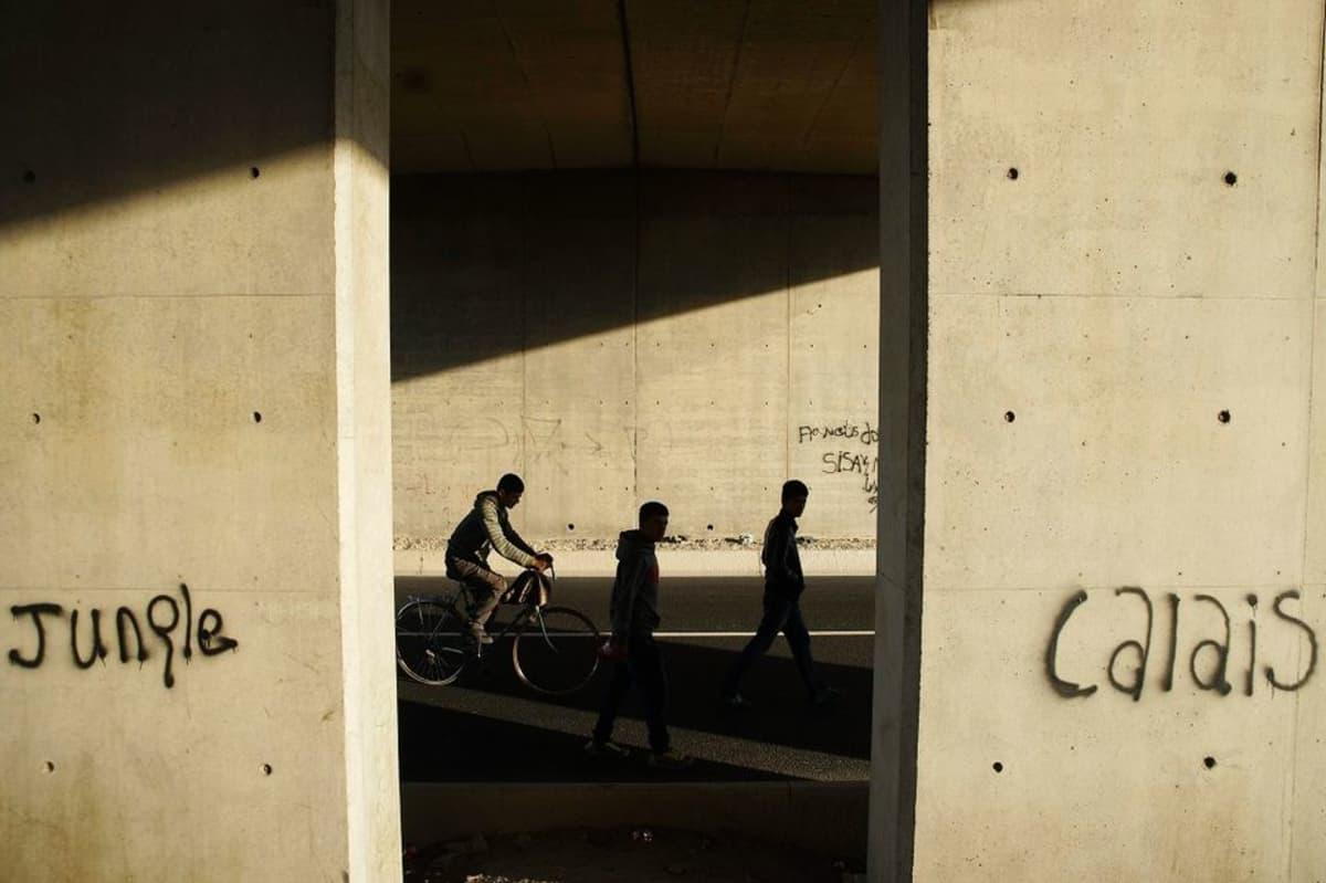 """Käveleviä ja pyöräilevä miehiä betonipilarien väleissä. Pilarien graffiteissa lukee """"Calais"""" ja """"Jungle""""."""