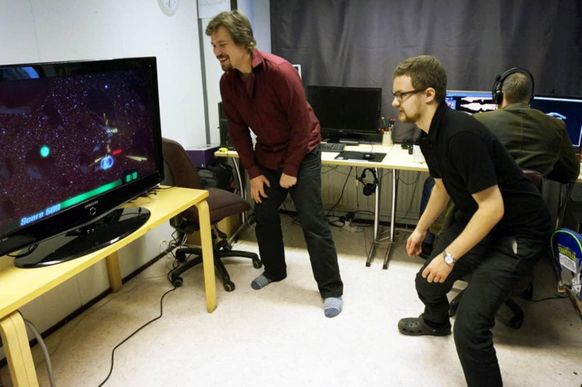 Peli- ja ohjemistofirman Caffeine Overdosen toimitusjohtaja JP Hakoluoto (oikealla) ja varatoimitusjohtaja Ville Nyyssölä pelaavat avaruuspeliä.