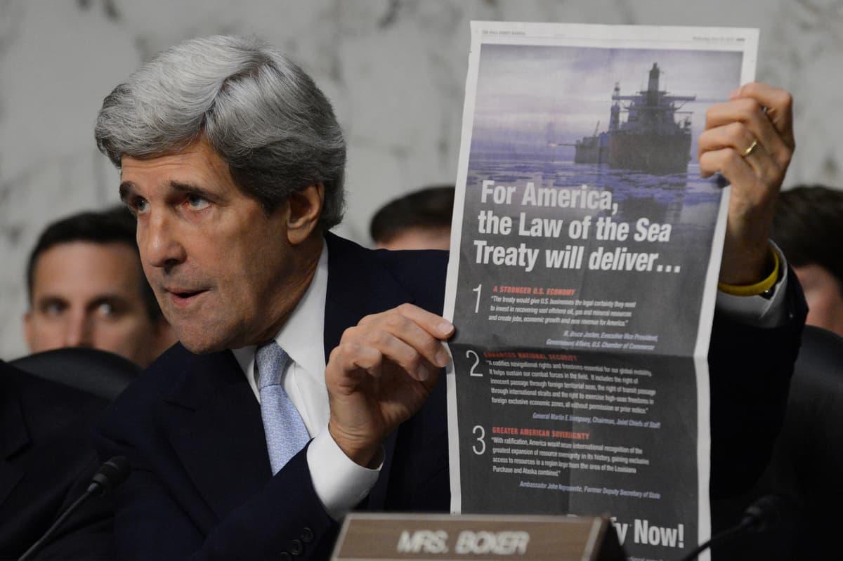 John Kerry pitelee sanomalehteä, joka kannattaa sopimusta.