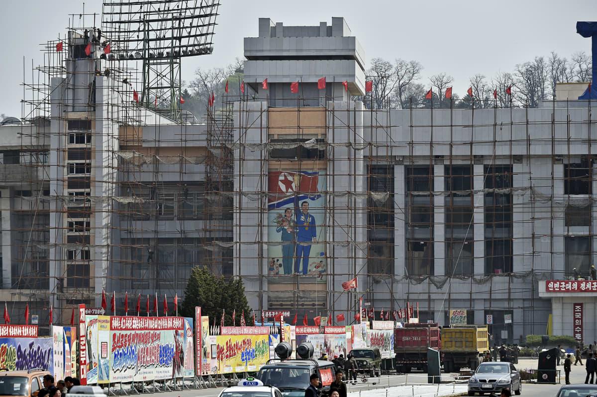 Propagandajulisteita rakenteille olevan stadionin edustalla.