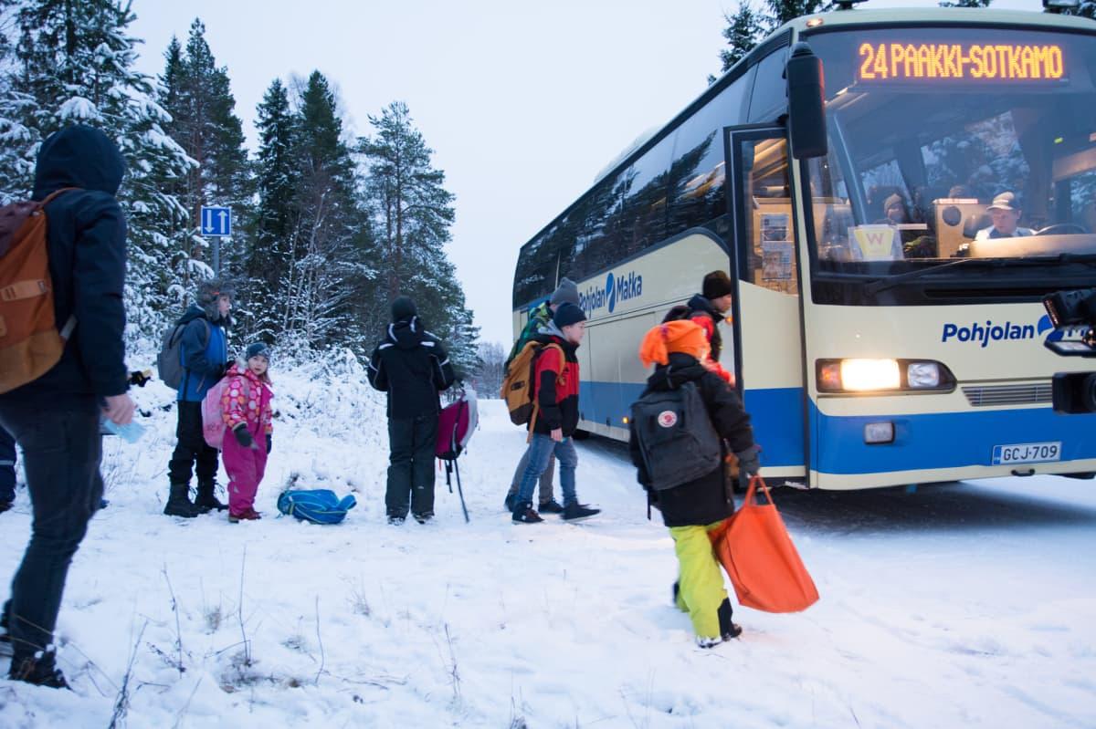 Koululaisia nousemassa linja-auton kyytiin talvella.