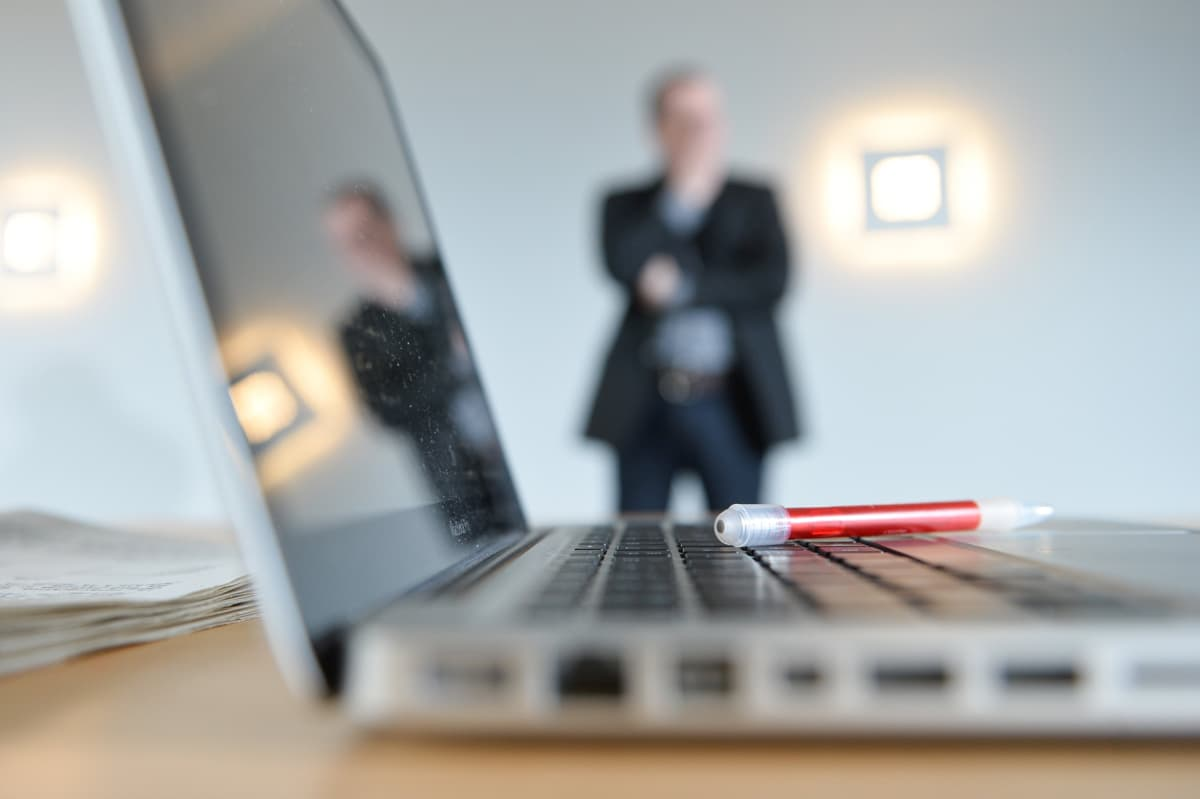 Kannettava tietokone etualalla ja tuntematon mies näkyy taustalla.