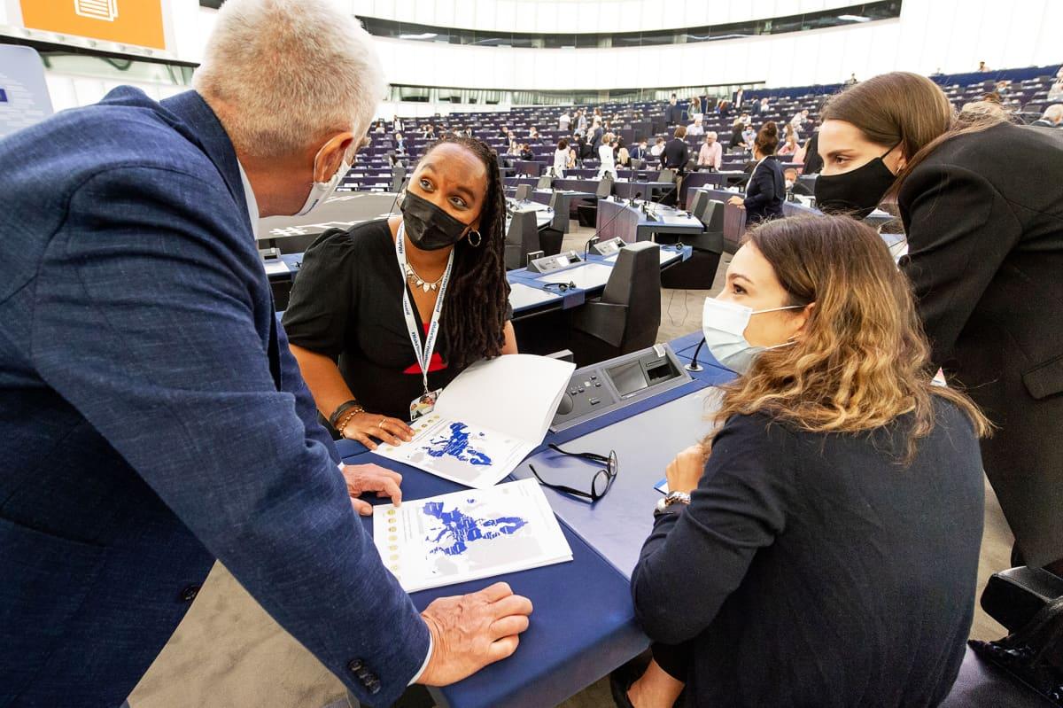 CoFoE -konferenssin osallistujia keskustelemassa parlamentin istuntosalissa.