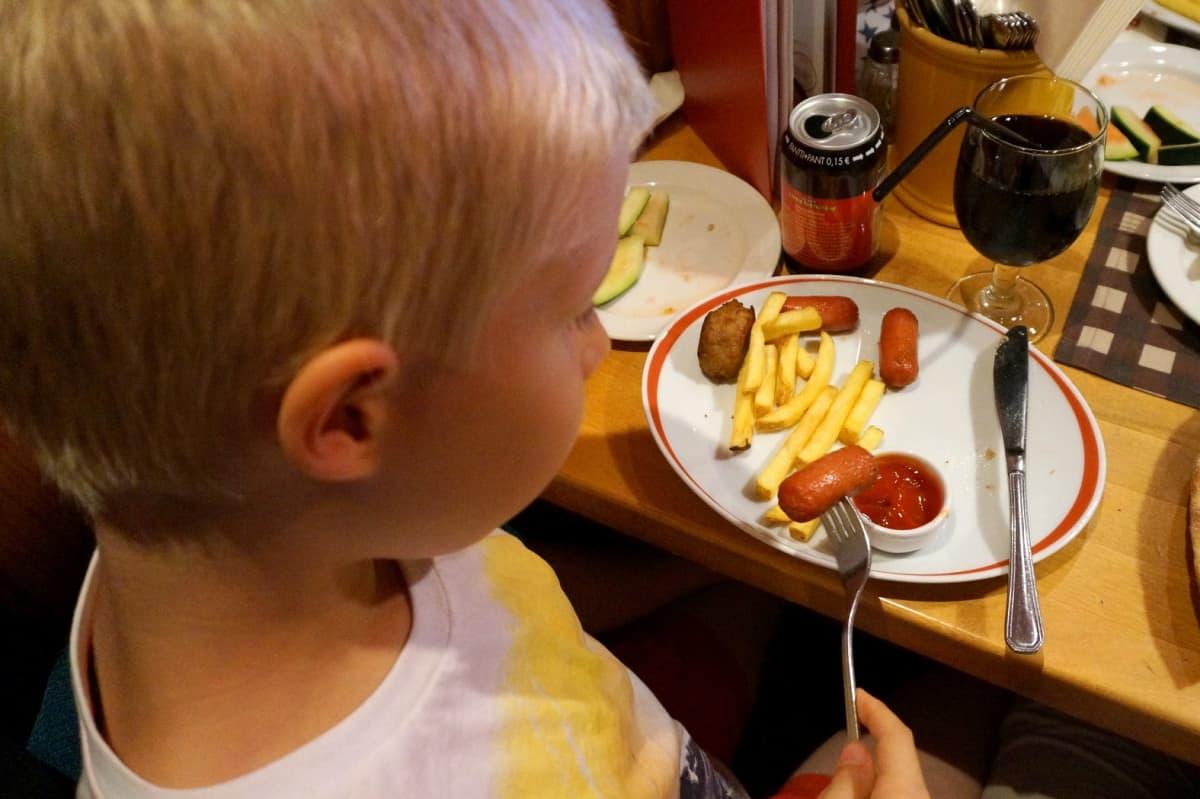 Poika syö lastenateriaa ravintolapöydässä