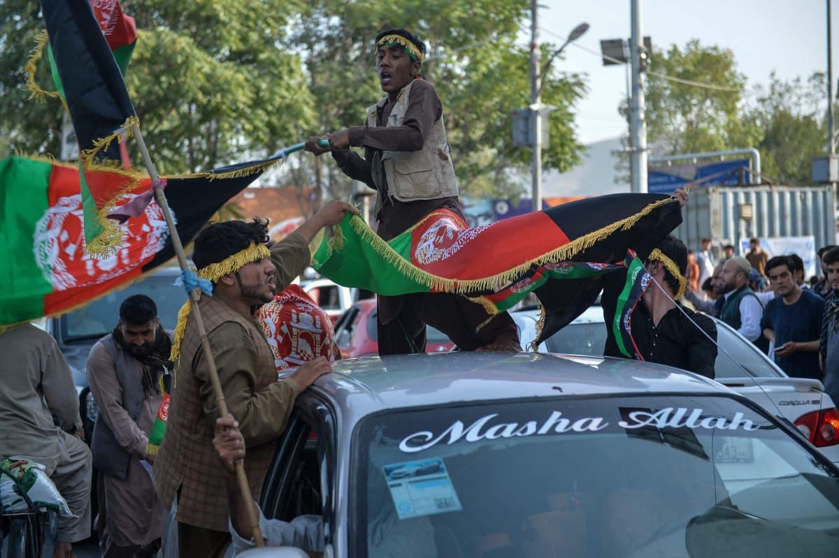Ihmiset kantavat Afganistanin lippua.