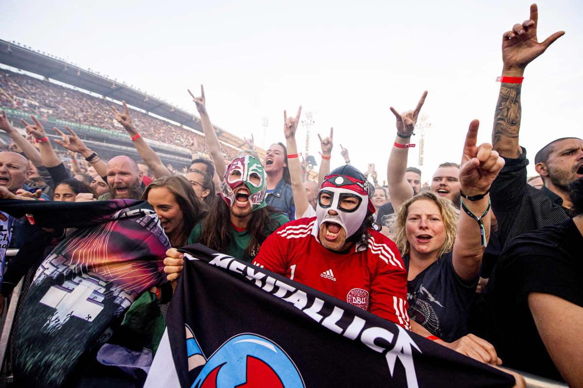 Metallica-fanit maskeineen ja banderolleineen keikalla sormet ojossa.