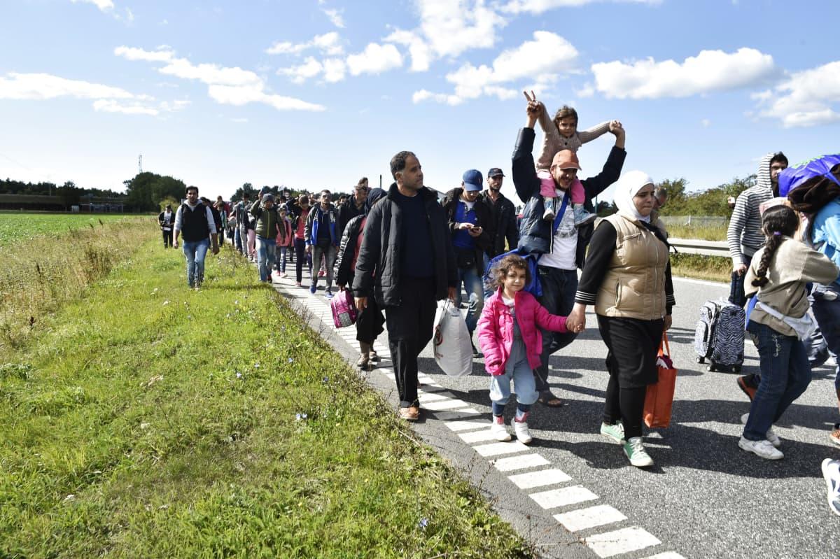 Ihmisiä kävelee tietä pitkin.