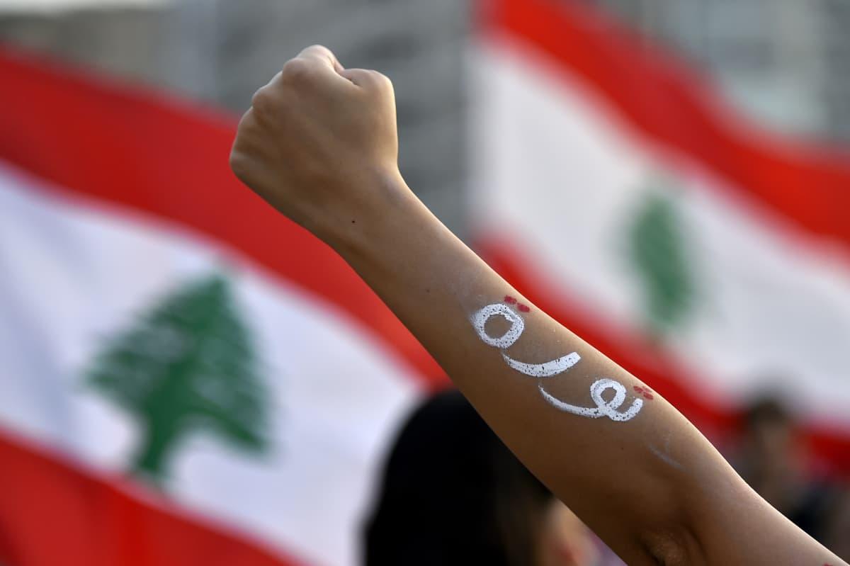 Nyrkkiin puristunut käsi. Taustalla Libanonin lippu.