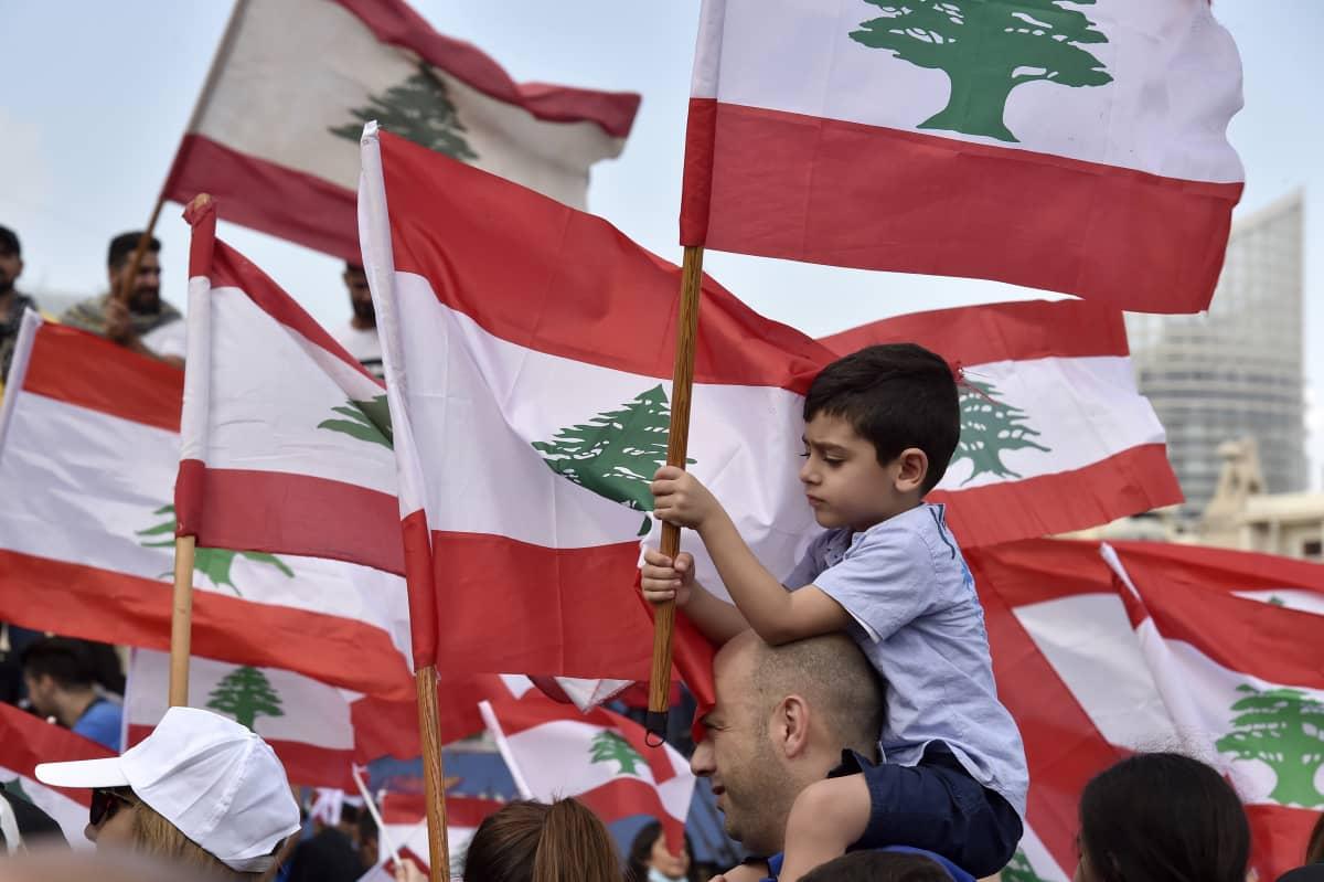 Miehen hartioilla istuva poika pitelee Libanonin lippua.
