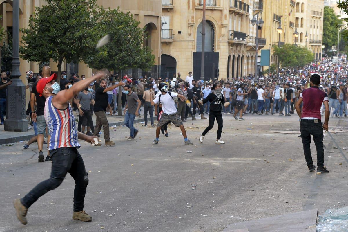 Mielenosoittajat heittävät kiviä kadulla Beirutissa, Libanonissa. Taustalla näkyy suuri joukko mielenosoittajia.