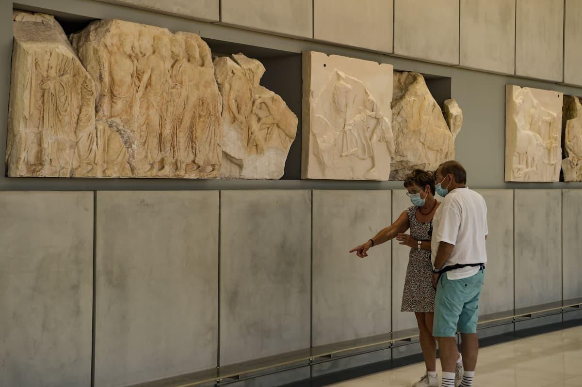 Mies ja nainen tarkastelevat reliefejä seinällä.