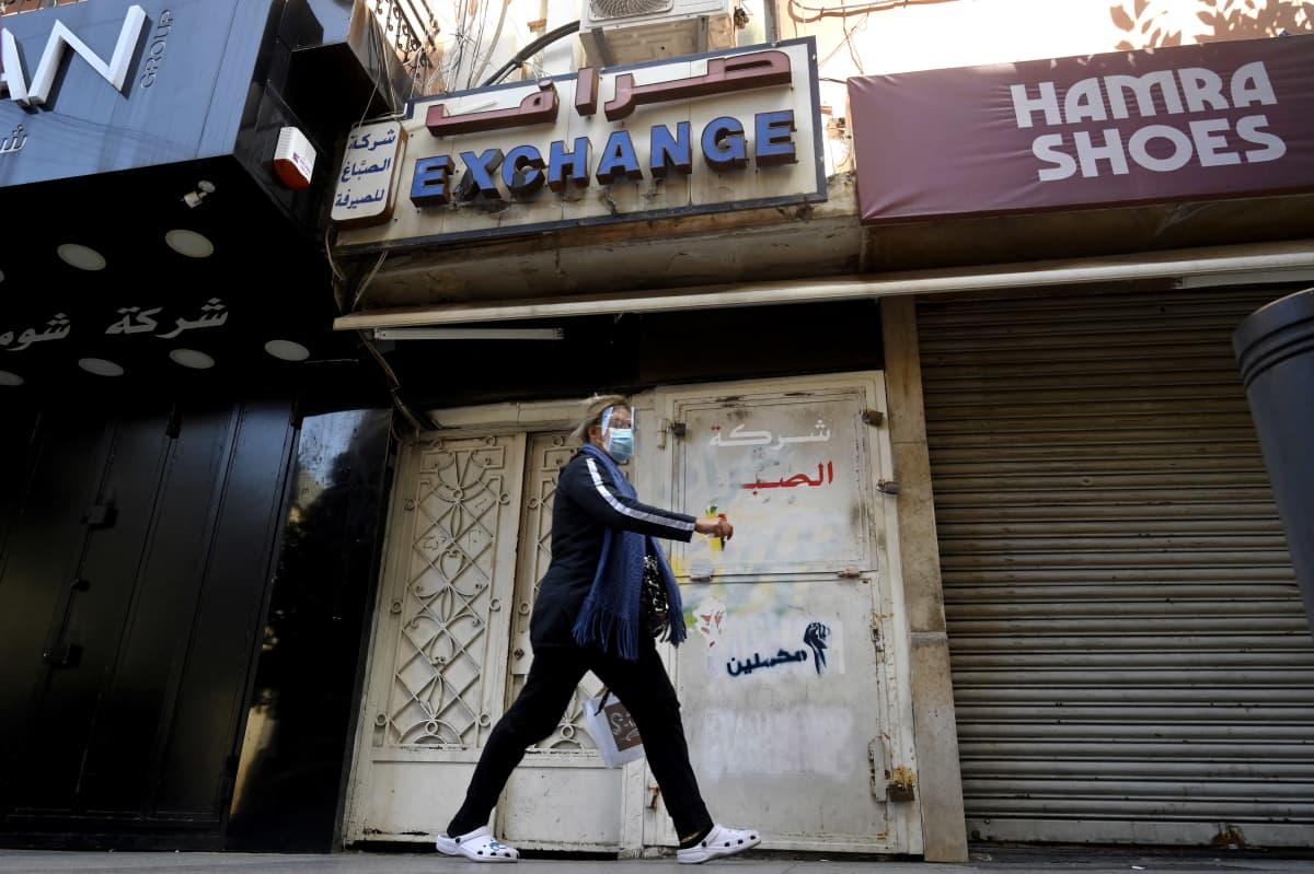 Nainen kävelee kiinni olevan valuutanvaihdon ohitse Beirutissa.   A woman walks in front of a closed currency exchange shop at Hamra street in Beirut, Lebanon, 17 March 2021.