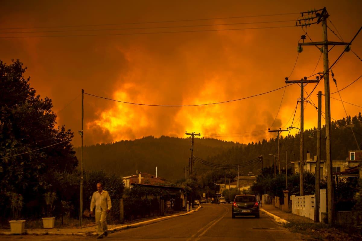 Asukas kävelee kadulla metsäpalon riehuessa kukkuloilla taustalla.
