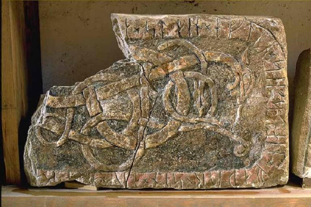 Murtunut kivenkappale, jonka reunalla on riimukirjoitusta ja keskellä ornamenttikuvio.