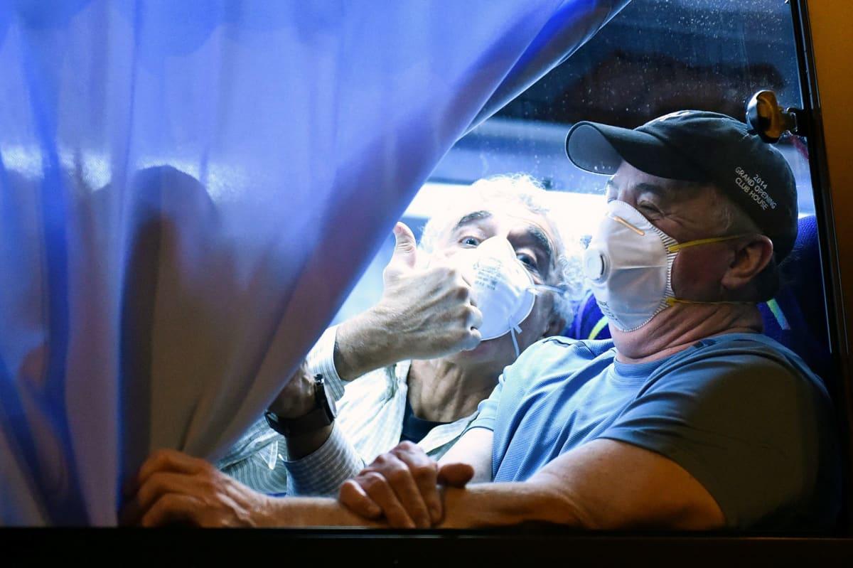 Mies näyttää peukkua valokuvaajalle bussin ikkunasta.
