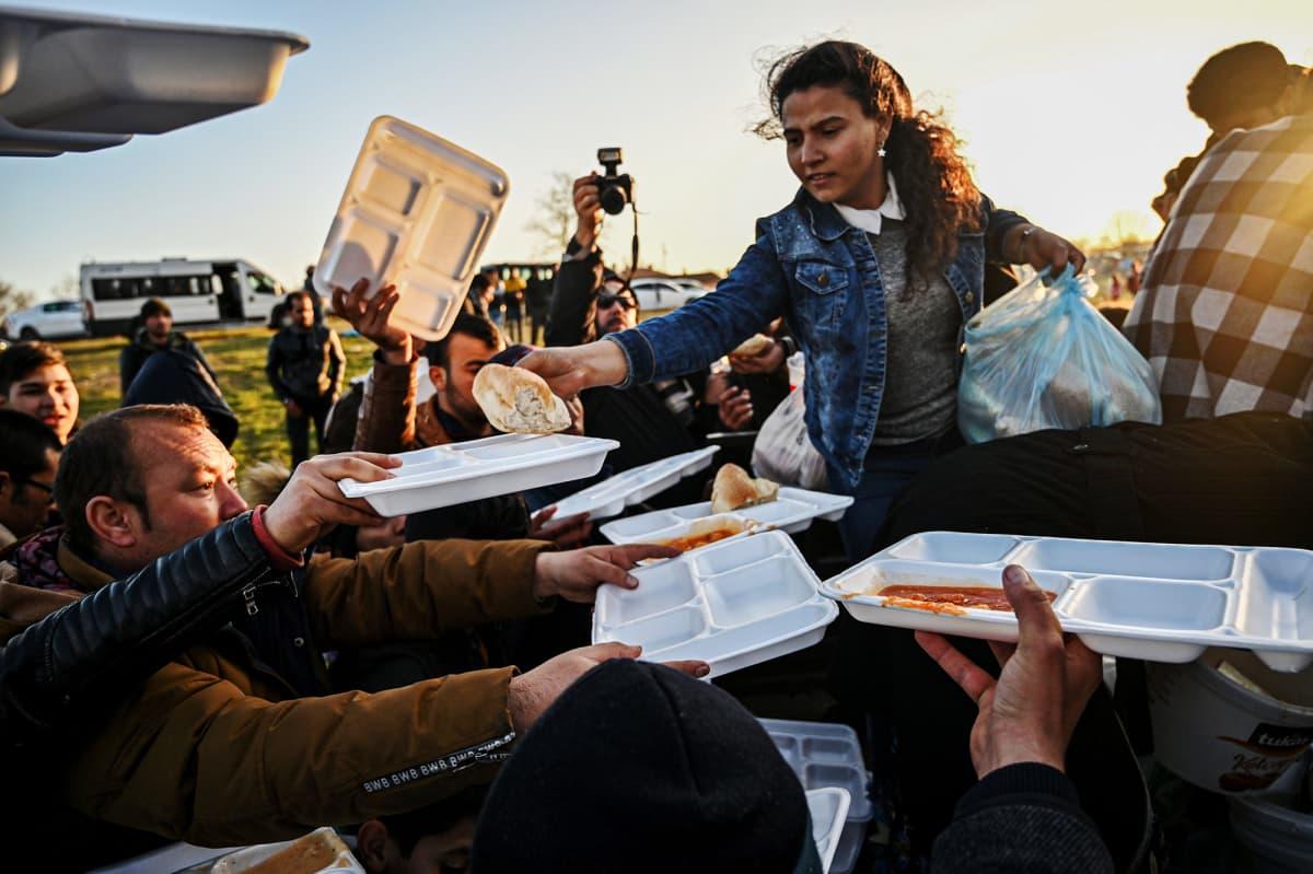 Kuvassa siirtolaisille jaetaan ruokaa Turkin Edirnen lähellä.