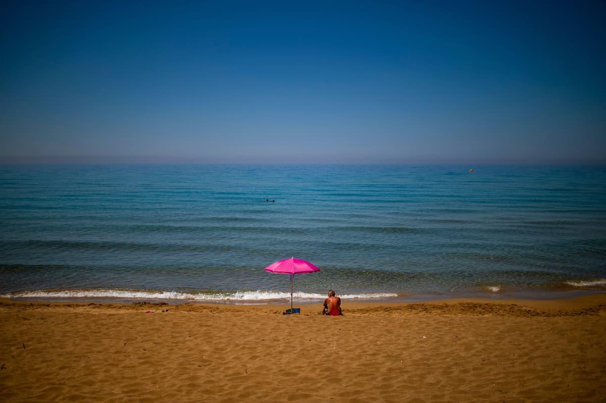 Kuvassa mies istuu yksin rannalla Kreikassa.