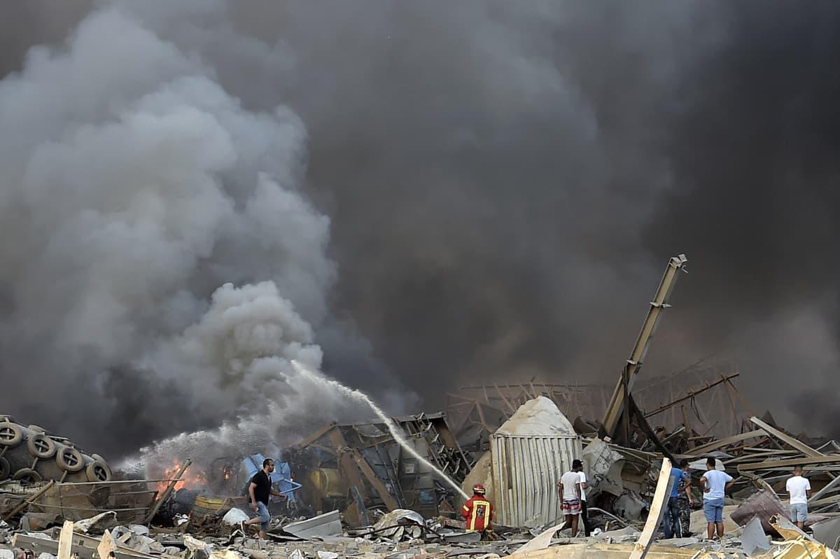 Palomiehet sammutavat räjähdyksen jälkipaloja.