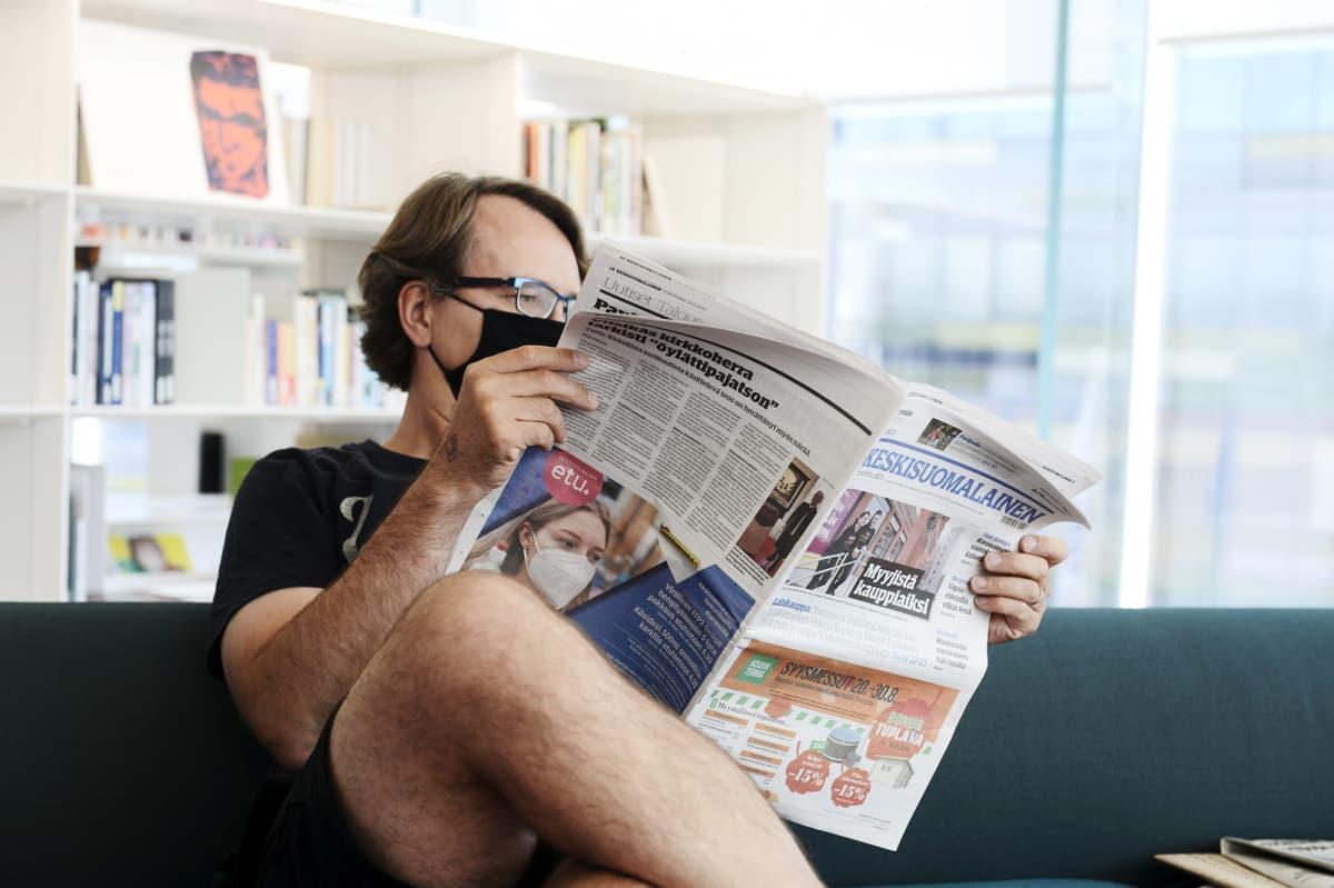 Mies maski kasvoillaan lukee Keskisuomalainen-sanomalehteä keskustakirjasto Oodissa.
