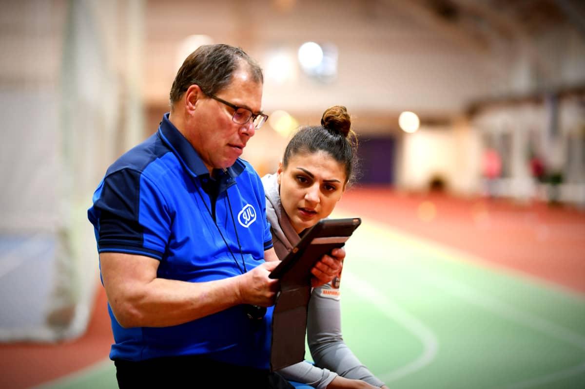 Nooralotta Neziri analyserar loppet från en pekplatta tillsamans med tränaren Petteri Jouste