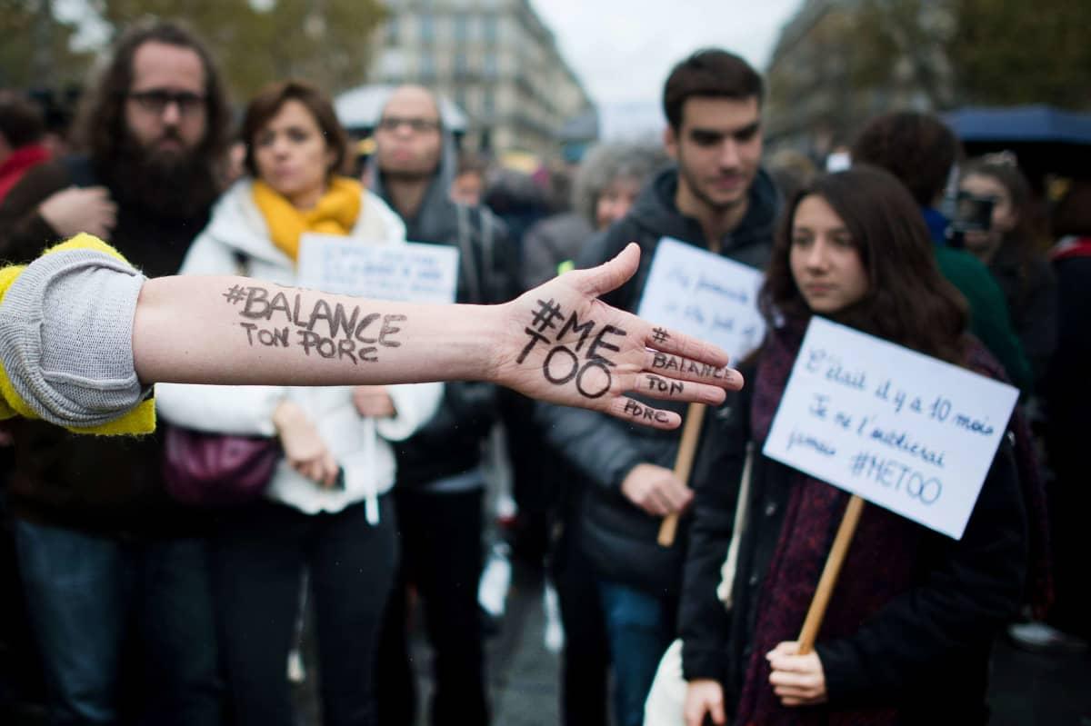 Käsi, jossa lukee #metoo ja #BalanceTonPorc. Taustalla mielenosoittajia.